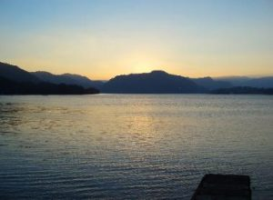 Lake at sunset with hills in the background