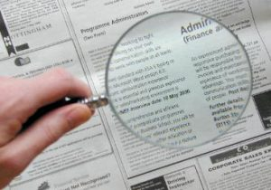 Magnifing glass looking at a newspaper article